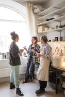 Happy female colleagues standing with coffee cups while talking at ceramics store 11081016702| 写真素材・ストックフォト・画像・イラスト素材|アマナイメージズ