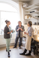 Happy female colleagues standing with coffee cups while talking at ceramics store 11081016703| 写真素材・ストックフォト・画像・イラスト素材|アマナイメージズ