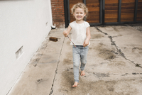 Full length portrait of happy girl playing with magic wand outside house