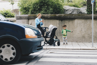 Mother using mobile phone while standing with son and baby stroller on sidewalk at city