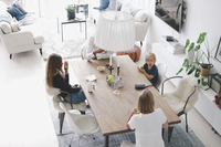 High angle view of family sitting at table in living room