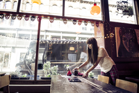 A young woman clearing a table in a coffee shop in Manchester. 11082001361| 写真素材・ストックフォト・画像・イラスト素材|アマナイメージズ