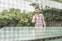 A twelve year old boy playing table tennis outside. 11082001716| 写真素材・ストックフォト・画像・イラスト素材|アマナイメージズ