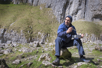 A mountaineer sitting eating food in rugged terrain. 11082001747| 写真素材・ストックフォト・画像・イラスト素材|アマナイメージズ