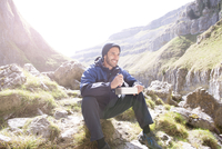 A mountaineer sitting eating food in rugged terrain. 11082001753| 写真素材・ストックフォト・画像・イラスト素材|アマナイメージズ
