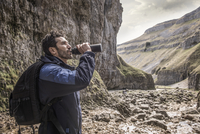 A mountaineer drinking from his water bottle fin rugged terrain. 11082001781| 写真素材・ストックフォト・画像・イラスト素材|アマナイメージズ