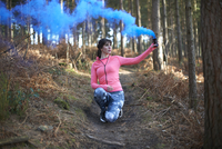 A woman lets off a flare in the woods 11082002285| 写真素材・ストックフォト・画像・イラスト素材|アマナイメージズ