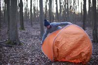 A man puts up a tent in the woods 11082002294| 写真素材・ストックフォト・画像・イラスト素材|アマナイメージズ