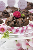 Chocolate muffins on glass cake stand decorated with flowers 11084000406| 写真素材・ストックフォト・画像・イラスト素材|アマナイメージズ