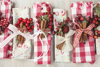 Hand-crafted, gingham and floral napkins decorated for Christmas with ribbons, berries and cinnamon sticks 11084000453| 写真素材・ストックフォト・画像・イラスト素材|アマナイメージズ
