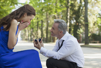 Man with engagement ring proposing to surprised woman
