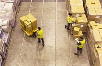 Workers carting boxes in warehouse 11086004556| 写真素材・ストックフォト・画像・イラスト素材|アマナイメージズ