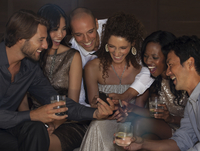 Friends using cell phone at party 11086005222| 写真素材・ストックフォト・画像・イラスト素材|アマナイメージズ