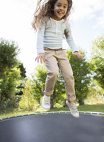 Girl jumping on trampoline outdoors