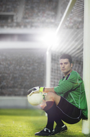 Goalie holding soccer ball by net