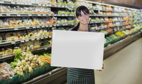 Clerk holding blank card in produce section of grocery store 11086015274| 写真素材・ストックフォト・画像・イラスト素材|アマナイメージズ