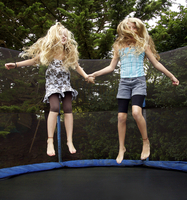 Girls jumping on trampoline outdoors