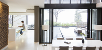Young man using laptop in modern kitchen, dining area with patio door and swimming pool in foreground 11086018219| 写真素材・ストックフォト・画像・イラスト素材|アマナイメージズ