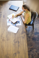 Creative businesswoman writing in notebook at table in office 11086021985| 写真素材・ストックフォト・画像・イラスト素材|アマナイメージズ