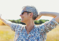 Enthusiastic senior woman with arms outstretched in sunny field 11086022836| 写真素材・ストックフォト・画像・イラスト素材|アマナイメージズ