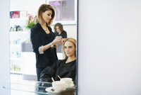 Hairdresser curling customer's hair in salon