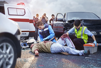 Rescue workers tending to bloody car accident victim in road 11086024914| 写真素材・ストックフォト・画像・イラスト素材|アマナイメージズ