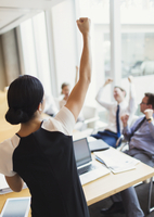 Exuberant businesswoman gesturing with fist and celebrating with colleagues in conference room