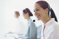 Smiling businesswoman talking on the phone with headset 11086026140| 写真素材・ストックフォト・画像・イラスト素材|アマナイメージズ