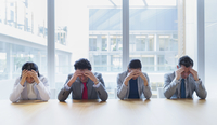 Stressed business people with heads in hands at conference table