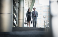 Corporate businessman and businesswoman descending stairs outdoors 11086026771| 写真素材・ストックフォト・画像・イラスト素材|アマナイメージズ