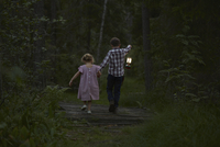 Brother and sister walking with lantern over footbridge in woods 11086027875| 写真素材・ストックフォト・画像・イラスト素材|アマナイメージズ