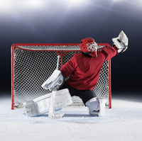 Hockey goalie in red uniform reaching for puck with glove at goal net