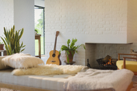 Guitar leaning near fireplace behind chaise in living room 11086028777| 写真素材・ストックフォト・画像・イラスト素材|アマナイメージズ