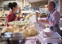 Deli worker offering cheese sample to woman in market