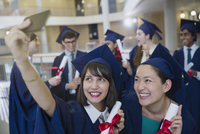 College women graduates in cap and gown taking selfie with diplomas