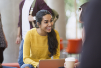 Smiling female college students with coffee and laptop 11086029657| 写真素材・ストックフォト・画像・イラスト素材|アマナイメージズ