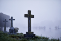 Crosses on gravestones in ethereal flooded foggy cemetery