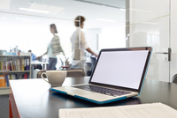 Laptop and coffee cup on desk with business people walking in background 11086030287| 写真素材・ストックフォト・画像・イラスト素材|アマナイメージズ