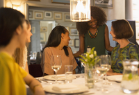 Smiling women friends dining and talking at restaurant table 11086031439| 写真素材・ストックフォト・画像・イラスト素材|アマナイメージズ