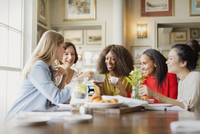 Smiling women drinking coffee and talking at restaurant table
