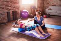 Fitness instructor helping young woman doing push-ups in gym studio