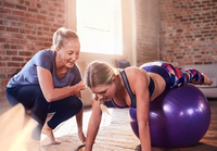 Fitness instructor helping young woman balancing on fitness ball in gym studio
