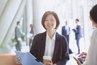 Portrait smiling businesswoman drinking coffee and reviewing paperwork in office lobby 11086032059| 写真素材・ストックフォト・画像・イラスト素材|アマナイメージズ