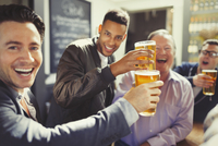 Enthusiastic men friends toasting beer glasses at bar