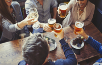 Overhead view friends celebrating, toasting beer and wine glasses at table in bar