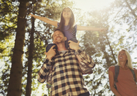 Father carrying daughter on shoulders, hiking in sunny woods 11086032516| 写真素材・ストックフォト・画像・イラスト素材|アマナイメージズ