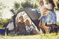 Parents watching happy daughters running around sunny campsite tent
