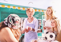 Senior female business owner serving ice cream to young women outside sunny food cart 11086032638| 写真素材・ストックフォト・画像・イラスト素材|アマナイメージズ