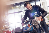 Male motorcycle mechanic wiping motorcycle in workshop 11086033721| 写真素材・ストックフォト・画像・イラスト素材|アマナイメージズ