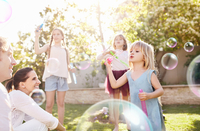 Parents watching daughters blowing bubbles in sunny back yard 11086033755| 写真素材・ストックフォト・画像・イラスト素材|アマナイメージズ